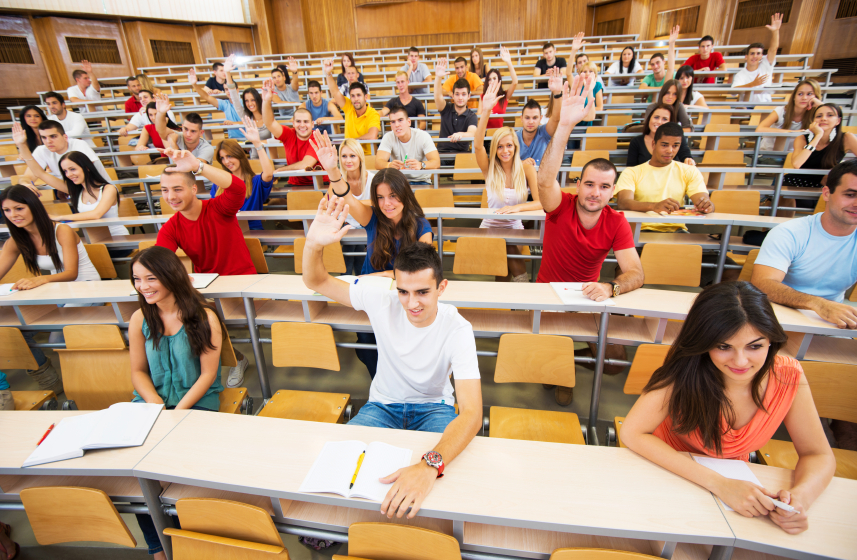 Students at lecture hall raising their hands to answer question.